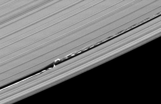 The waves in Saturns A ring are formed by the gravitational pull of tiny moon Daphnis, the bright dot (only 5 mi in diameter) in the gap just to the left of center. 